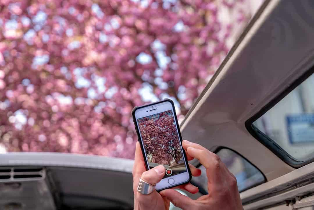 A hand holding a cellphone in front of a car